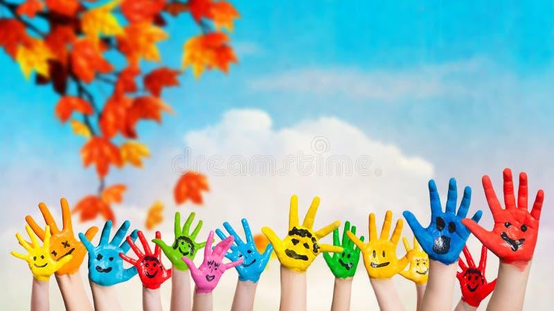 Molte mani colorate con gli smiley fotografie stock