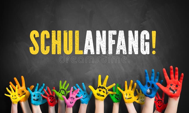 Molte mani dipinte dei bambini con il messaggio & il x22; di nuovo alla scuola! & x22; & x28; in German& x29; su una lavagna fotografie stock