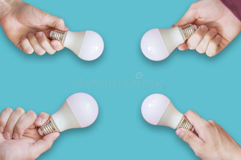 Molte mani multiple che tengono concetto creativo isolato f delle lampadine fotografia stock libera da diritti