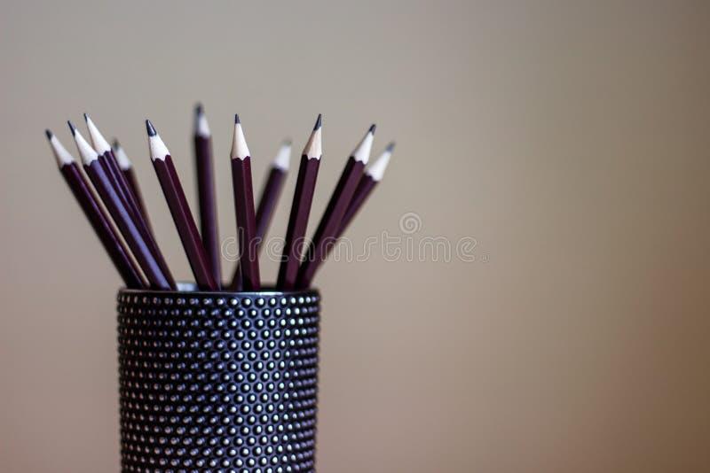 Molte matite della grafite che stanno in contenitore di vetro nero fotografie stock libere da diritti