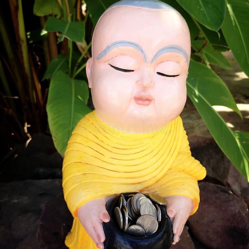Molte monete nella ciotola di Little Monk immagine stock libera da diritti