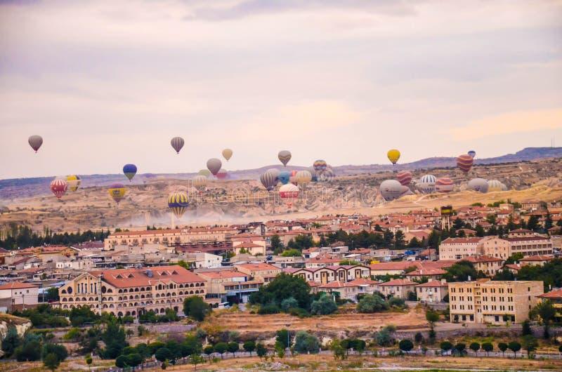 Molte mongolfiere che sorvolano paesaggio roccioso nella città di Goreme a Cappadocia fotografia stock libera da diritti