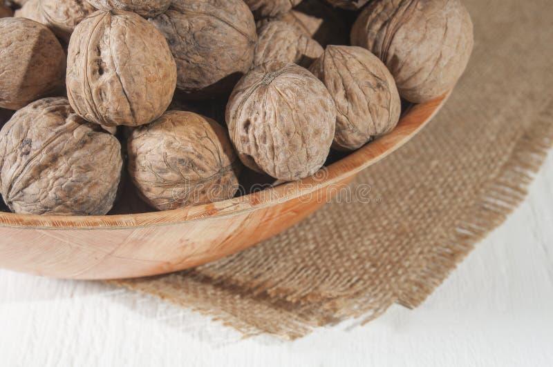 Molte noci si trovano in una ciotola Ciotola su tela da imballaggio Tabella di legno bianca fotografia stock libera da diritti