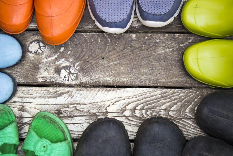 Molte paia delle scarpe di estate: Stivali di gomma, pantofole, galosce su un pavimento di legno d'annata, immagini stock libere da diritti