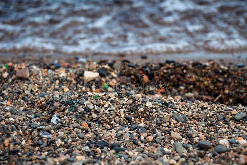 Molte piccole pietre sulla riva di un lago pulito fotografie stock