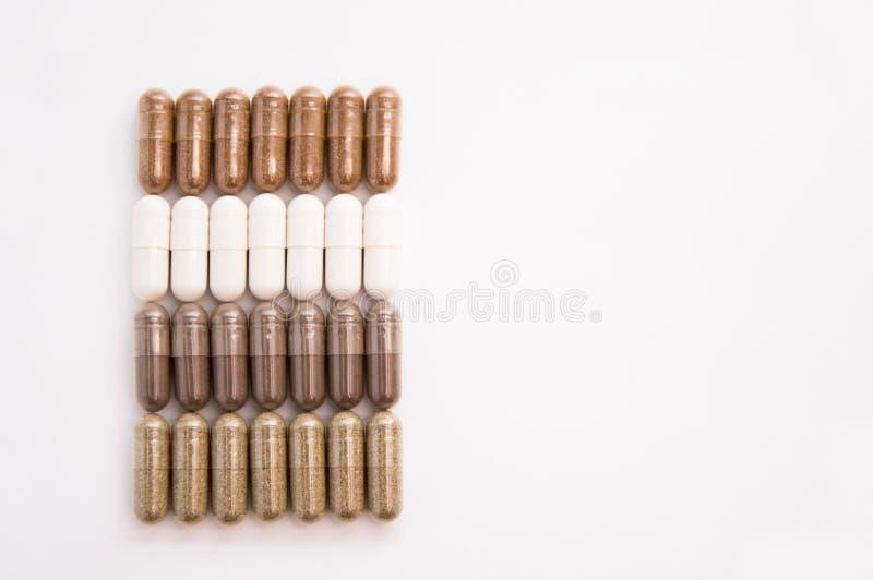 Molte pillole della capsula rovesciate da un barattolo su un fondo bianco fotografie stock