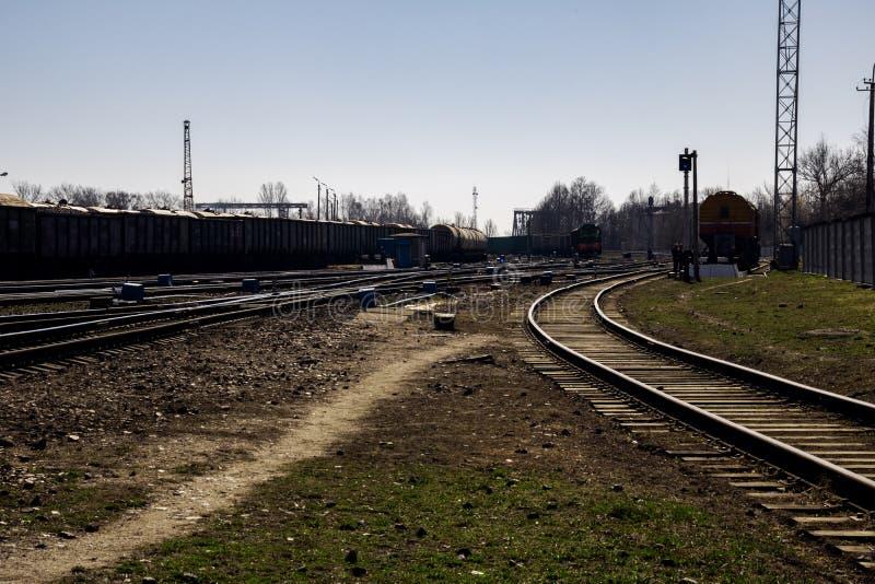Molte rotaie della ferrovia vicino alla stazione ed al cielo blu immagine stock