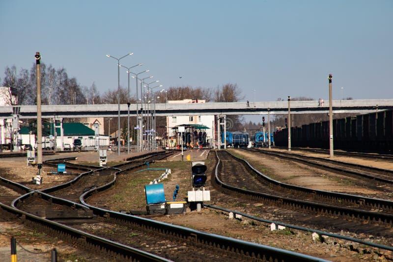 Molte rotaie della ferrovia vicino alla stazione ed al cielo blu fotografia stock libera da diritti