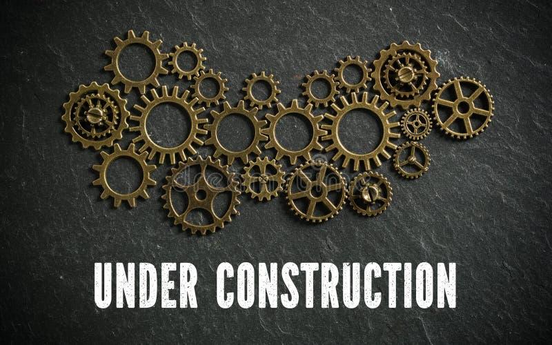 Molte ruote dentate che simbolizzano una macchina complessa e il ` in costruzione del ` del messaggio immagine stock libera da diritti