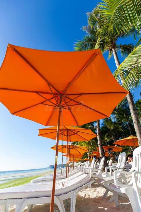 Molte sedie ed ombrello sulla spiaggia immagine stock