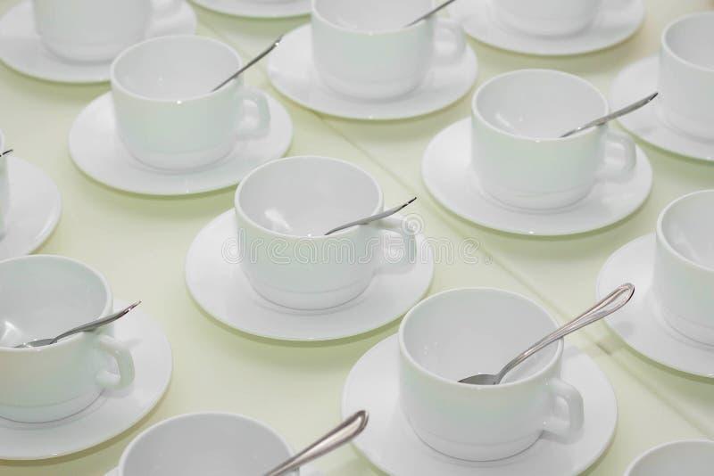 molte tazze bianche vuote di tè sulla tavola immagine stock libera da diritti
