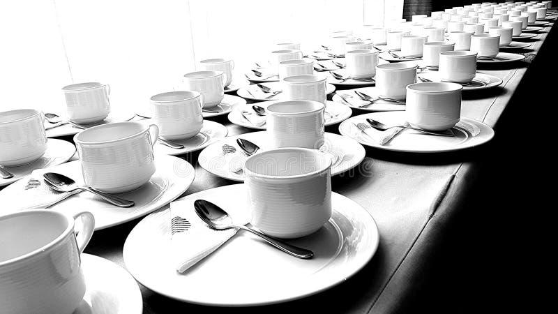 Molte tazze su una tavola lunga fotografie stock libere da diritti