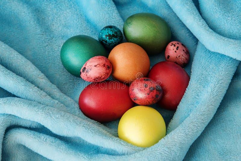 Molte uova di Pasqua colorate delle dimensioni differenti su una coperta molle blu fotografia stock libera da diritti
