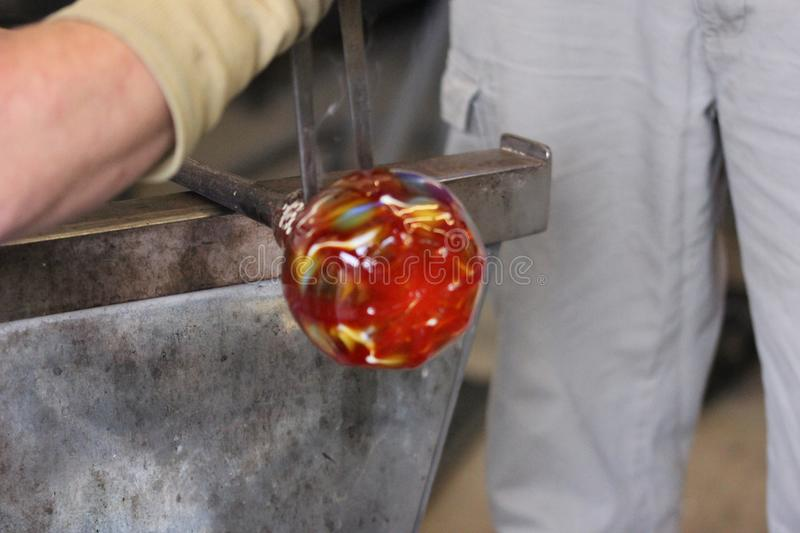 Molten glass on a metal rod for glass blowing macro royalty free stock images