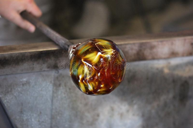 Molten glass on a metal rod for glass blowing macro royalty free stock image