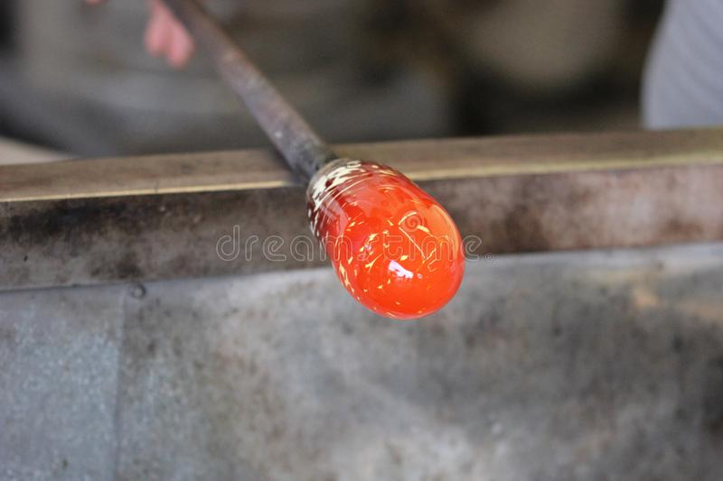Molten glass on a metal rod for glass blowing macro. Molten glass on a metal rod being shaped for glass blowing up close macro stock photo