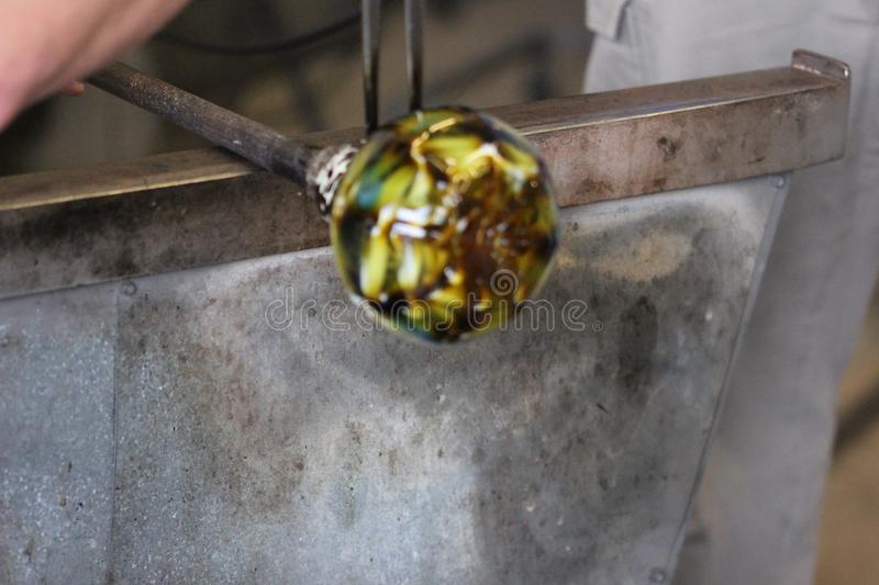 Molten glass on a metal rod for glass blowing macro. Molten glass on a metal rod being shaped for glass blowing up close macro royalty free stock photos
