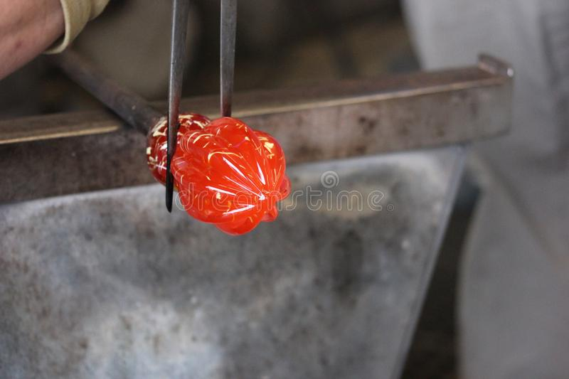 Molten glass on a metal rod for glass blowing macro. Molten glass on a metal rod being shaped for glass blowing up close macro stock images