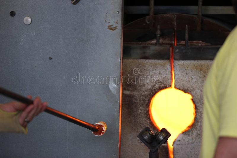 Molten glass on a metal rod for glass blowing macro. Molten glass on a metal rod for glass blowing up close macro stock images