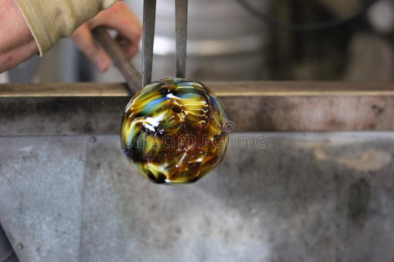 Molten glass on a metal rod for glass blowing macro. Molten glass on a metal rod being shaped for glass blowing up close macro royalty free stock images