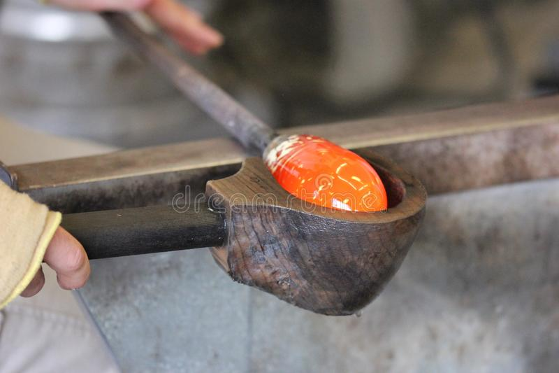 Molten glass on a metal rod for glass blowing macro. Molten glass on a metal rod being shaped for glass blowing up close macro stock photos