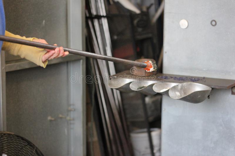 Molten glass on a metal rod for glass blowing. Molten glass on a metal rod getting color for glass blowing royalty free stock photo