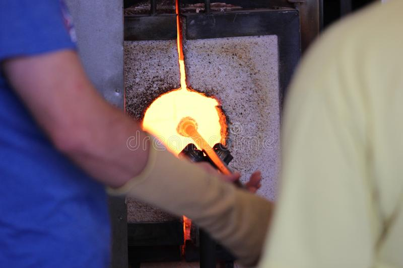 Molten glass on a metal rod in a furnace for glass blowing macro. Molten glass on a metal rod in a glowing furnace for glass blowing up close macro royalty free stock image