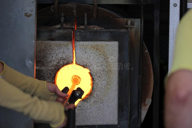 Molten glass on a metal rod in a furnace for glass blowing macro. Molten glass on a metal rod in a glowing furnace for glass blowing up close macro royalty free stock photos