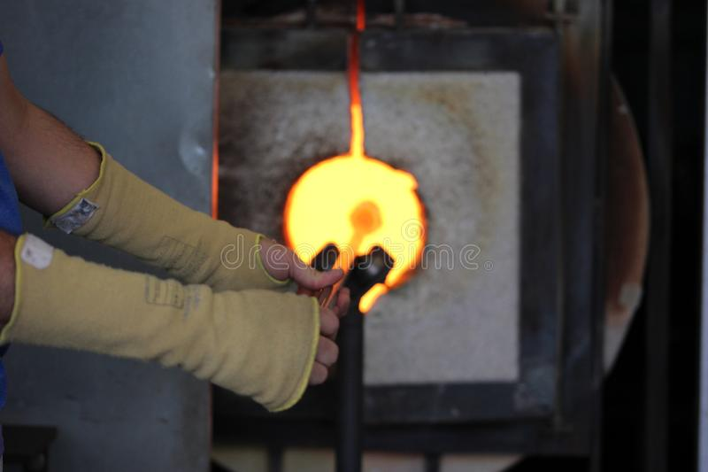 Molten glass on a metal rod in a furnace for glass blowing macro stock photos