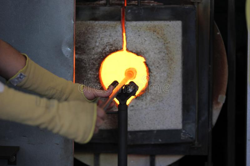 Molten glass on a metal rod in a furnace for glass blowing macro. Molten glass on a metal rod in a glowing furnace for glass blowing up close macro royalty free stock photo