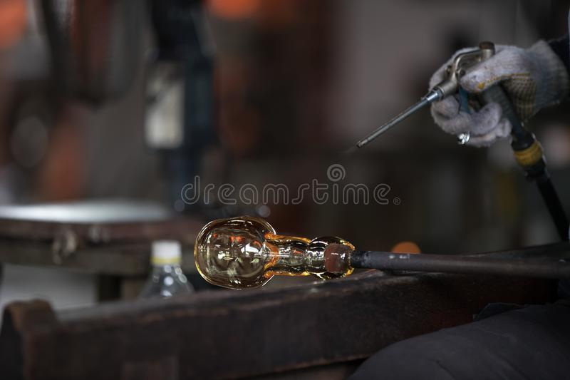 Molten glass on a metal rod. For glass blowing stock images