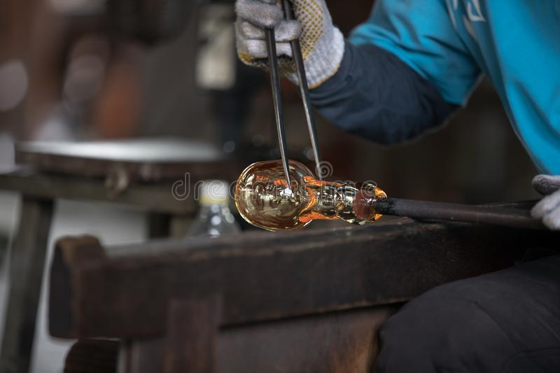 Molten glass on a metal rod. For glass blowing stock photos