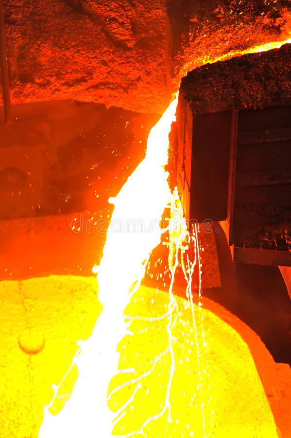 Molten hot steel. Foundry - molten metal poured from ladle for casting stock photography