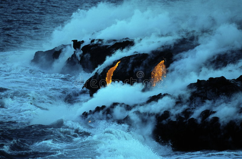 Molten Lava and the sea. Steam rises in this powerful image as hot, molten lava from Kileauea Volcano in Hawaii flows into the cooling sea royalty free stock photo