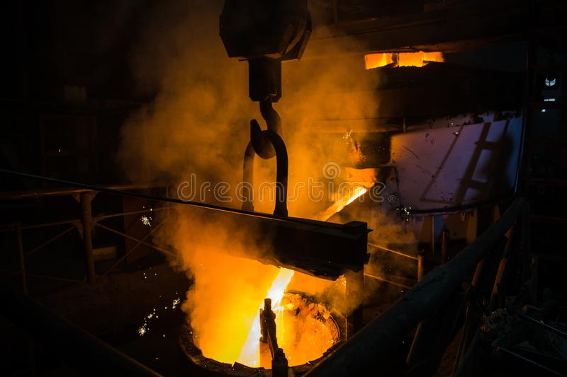 Molten steel pouring. Liquid hot metal of steel spills out of the ladle at steel factory. royalty free stock image