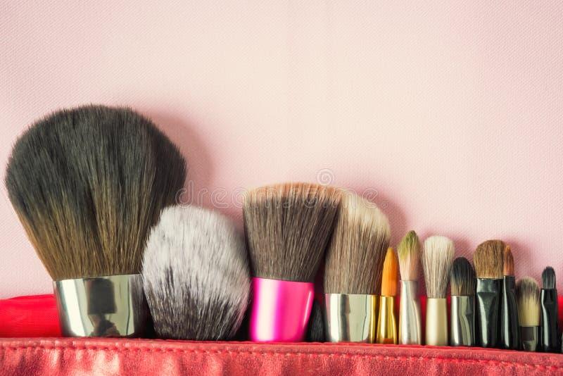 Molti adattano la spazzola per trucco o il cosmetico in borsa rossa sull'vago su fotografia stock libera da diritti