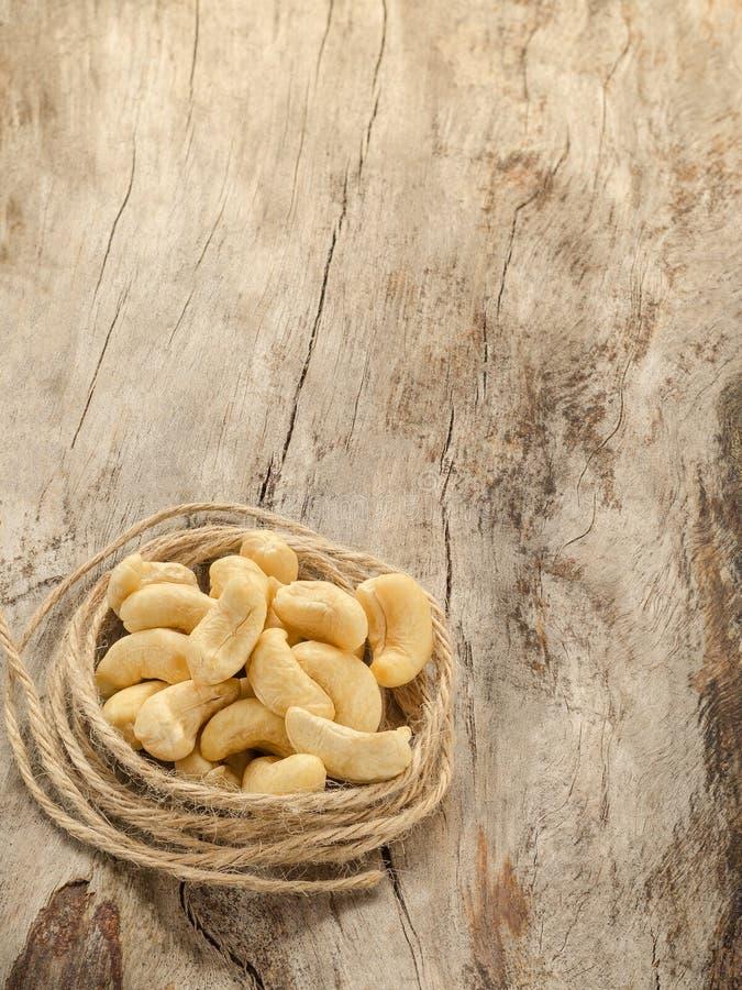 Molti anacardii con cordicella su legno invecchiato fotografia stock libera da diritti