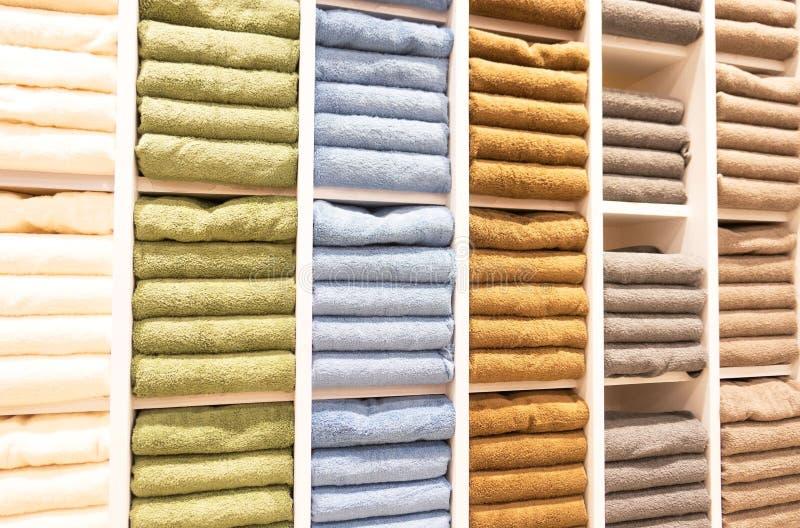 Molti asciugamani variopinti sta piegando negli shelfs al deposito da vendere fotografia stock