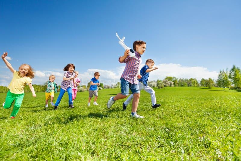 Molti bambini che corrono e giocattolo dell'aeroplano della tenuta del ragazzo fotografia stock