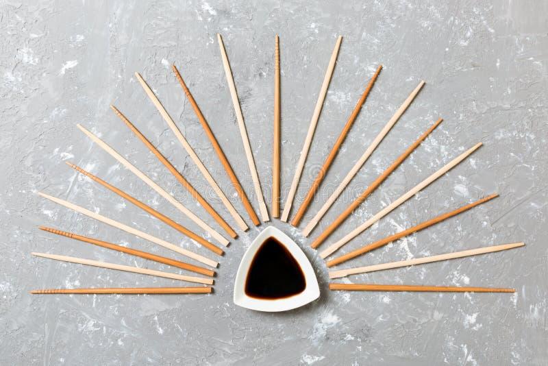 Molti bastoncini di bambù con la salsa di soia sul fondo di pietra del cemento nero, vista superiore con lo spazio della copia mo fotografia stock