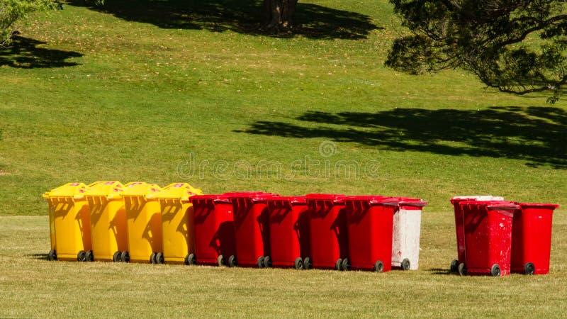Molti bidoni della spazzatura gialli e rossi al dominio di Auckland, Nuova Zelanda immagine stock libera da diritti