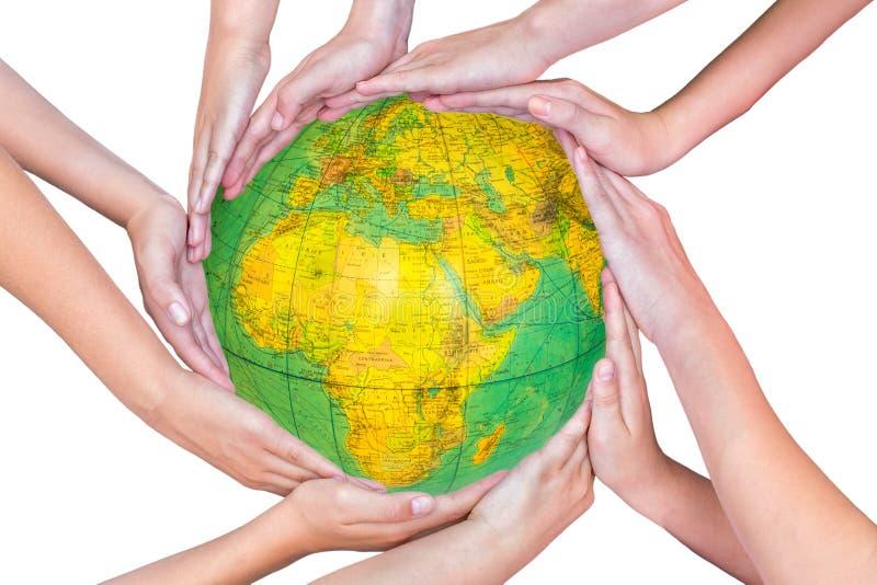Molti braccia dei bambini con le mani che tengono globo immagine stock