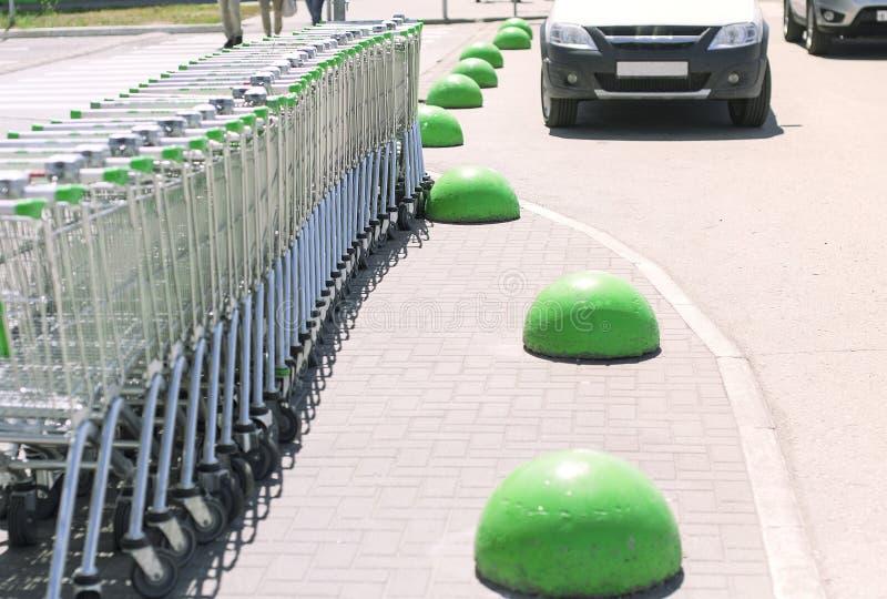 Molti carretti della drogheria parcheggiati vicino al centro commerciale sull'asfalto con gli emisferi di pietra verdi immagini stock libere da diritti