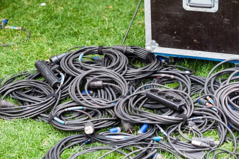 Molti cavi elettrici neri in verde sull'erba fotografia stock