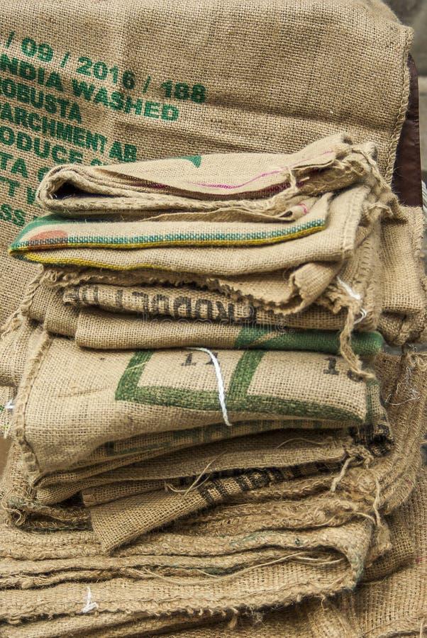 Molti chicchi di caffè vuoti insacca piegato e trovandosi su un mucchio un sacco appende nei precedenti con la stampa parziale no immagini stock libere da diritti