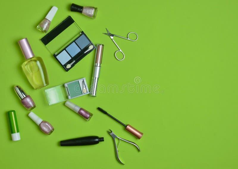 Molti cosmetici obietta per l'applicazione del trucco su un fondo verde What& x27; s nel women& x27; borsa del cosmetico di s? fotografia stock libera da diritti