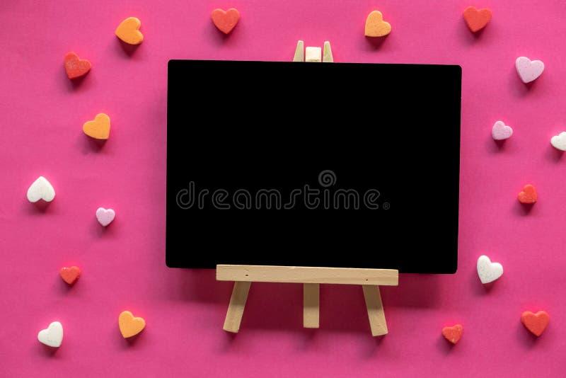 Molti cuori intorno alla lavagna su fondo rosa, icona di amore, San Valentino fotografie stock libere da diritti