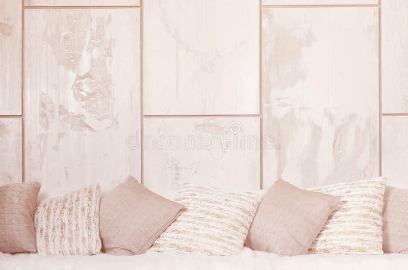 Molti cuscini si trovano sullo strato, che è coperto di grande velo della peluche contro lo sfondo di una parete di marmo immagine stock libera da diritti