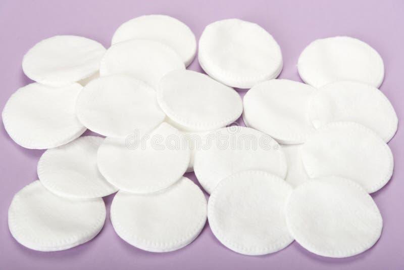 Molti dischi cosmetici del cotone su un fondo rosa immagine stock libera da diritti