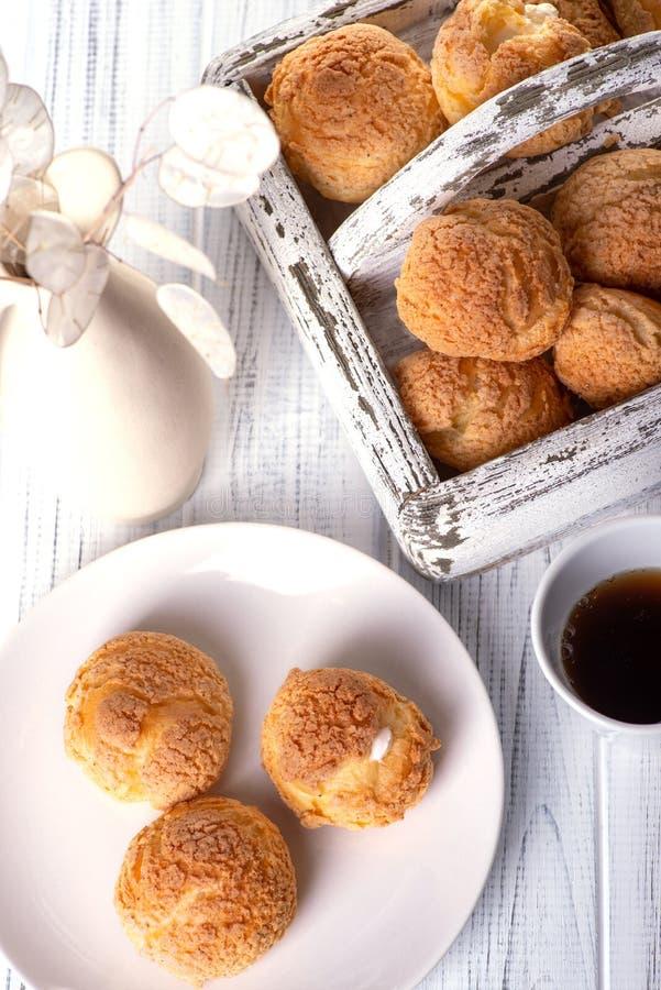 Molti dolci saporiti si trovano su un piatto rotondo su una tavola di legno bianca La brocca ceramica con un fiore e una scatola  immagine stock